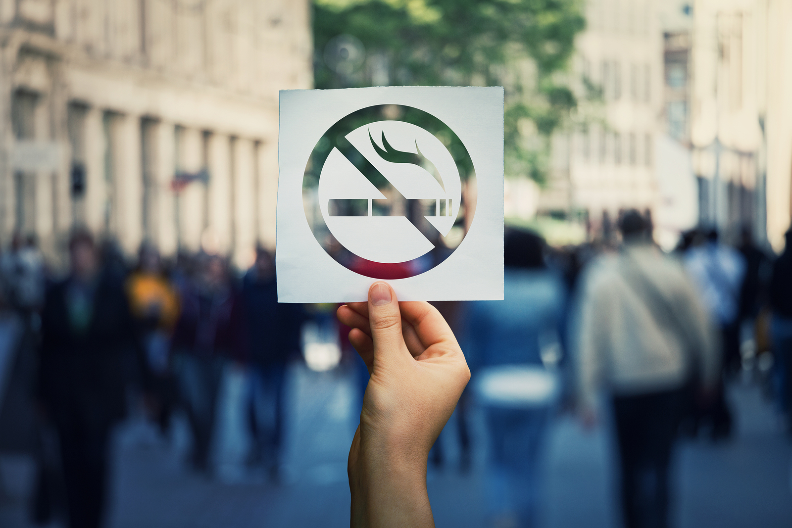 Hand Holding A Paper Sheet With No Smoking Sign Over A Crowded Street