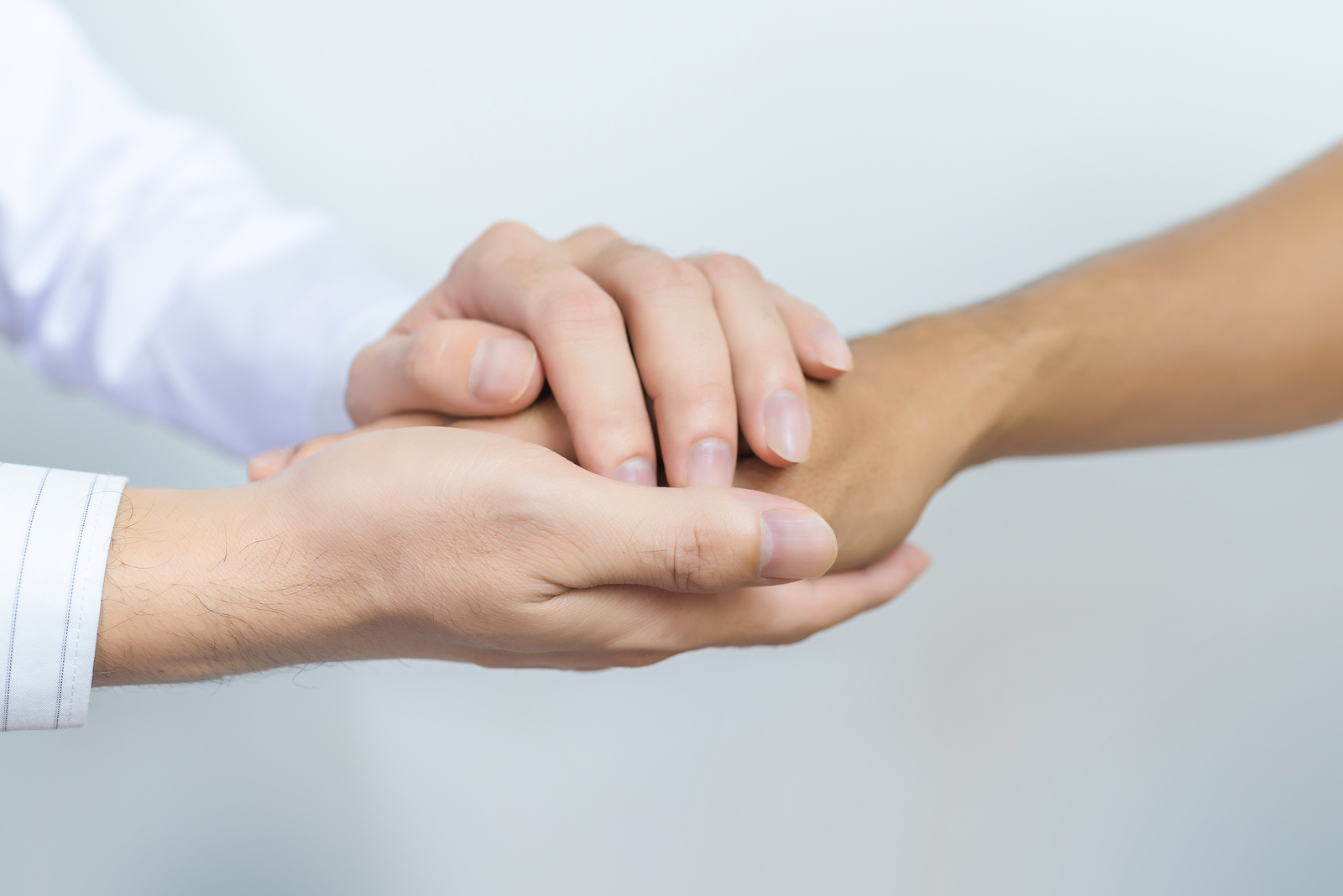 Two people holding hands for comfort. Doctor consoling relatives of patients in hospital concept.