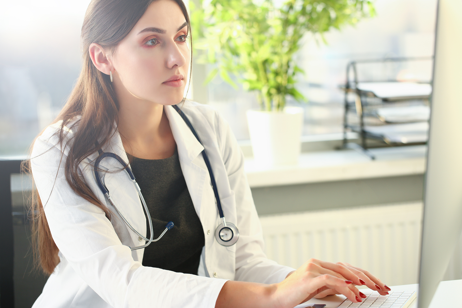 Young Female Doctor Uses Computer In Workplace.